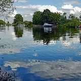 Seen from Attenborough Nature Reserve, Notts. An idyllic kind of scene, with clear mirror-like water, damselflies skimming across the surface (look closely) and moored boats.