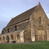 The hall of the Norman castle at Oakham, Rutland, UK, with All Saints church tower and spire in the background.