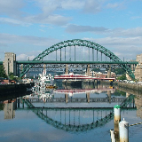 The Tyne Bridge across the River Tyne between Newcastle upon Tyne and Gateshead. Taken from the deck of the Gateshead Millennium Bridge, looking west. The Tyne Bridge is the compression arch bridge in green. Below and behind it is the Swing Bridge, in red. Behind that, in grey, is the High Level Bridge. Behind that is the w:Queen Elizabeth II Metro Bridge. You can just about see the pillars of the King Edward VII Bridge, which carries the mainline railway across the river into Newcastle Central station; and, I assure you, the Redheugh Bridge (a modern road bridge) is hidden behind them all. The boats on the Gateshead shore are the Archer class patrol vessels of the HMS Calliope shore establishment, and the permanently moored Tuxedo Princess floating nightclub (the former car ferry TSS Caledonian Princess). This photo appears to have been taken from the Tyne's easternmost bridge, the low-level, swivelling, pedestrian Millenium Bridge.