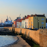 Town Wall, Hartlepool, Durham, England. Dating from the late 14th century the limestone wall once enclosed the whole of the medieval town. The terraced houses overlook the entrance to Victoria Docks in the background.